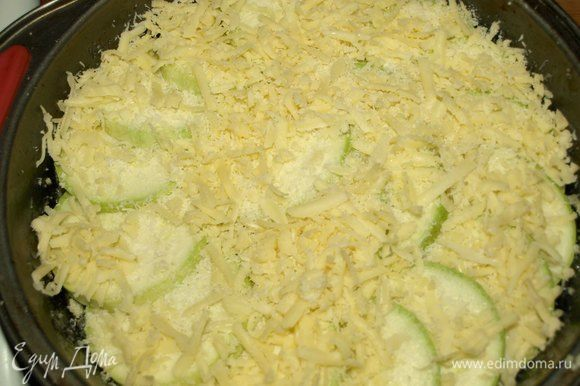 Дно формы (22 см) смазать оставшимся оливковым маслом. Посыпать частью тертого пармезана. Сверху выкладываем кабачки и посыпаем сыром. Немного оставить сыра для яично-овощной смеси. По желанию посолить.