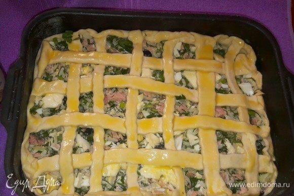 Сделать коврик на будущем пироге, смазать желтком и отправить в разогретую духовку на 20–30 минут.