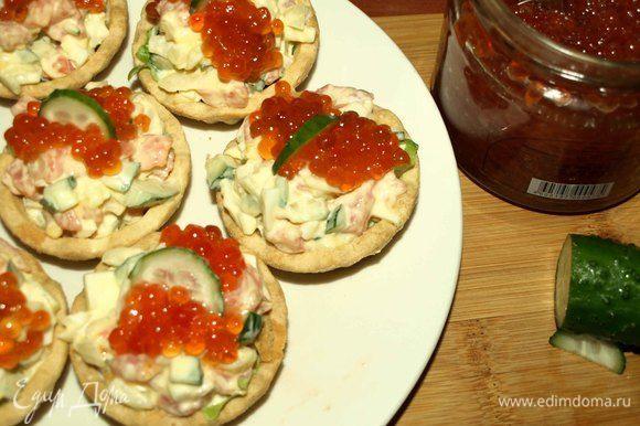Выкладываем салат в тарталетки. Сверху на салат выкладываем красную икру и украшаем кусочком огурца или листиком петрушки. Закуска готова.