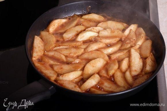 В большой сковороде растопить сливочное масло, выложить яблочные дольки, готовить яблоки на среднем огне примерно 10 минут — за это время сахар растопится, яблоки начнут карамелизоваться. Нужно следить, чтобы яблоки не превратились в кашу, то есть, готовить их до такого состояния, чтобы они были мягкие снаружи, чуть твердые внутри, хорошо держали форму.