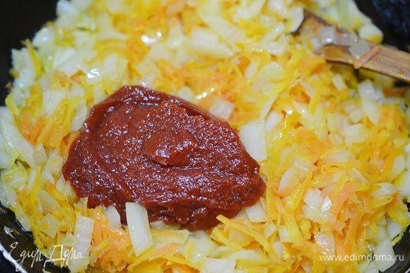 К луку с морковью добавьте томатную пасту. Обжарьте пару минут.