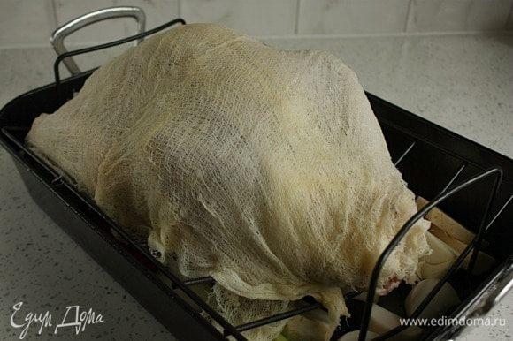 Вынуть замоченную марлю, слегка отжать и разложить на индейке как есть — в 4 слоя, прикрывая ноги. Поместить индейку в духовку ногами к задней стенке и готовить 30 минут (я добавила 0,5 ст. горячей воды к овощам, т.к. боялась, что они сгорят). Затем, используя кулинарную большую кисть, смочить марлю и неприкрытые части винно-масляной смесью (марля станет коричневой, не пугайтесь!). Убавить температуру до 180°С и готовить 1,5 часа, смачивая марлю каждые 30 минут. Из индейки будет выделяться мясной сок и жир, поэтому нужно следить за жидкостью в жаровне. Ее не должно быть много, чтобы птица не плавала в ней, но и не допускать, чтобы жидкость вообще отсутствовала. Можно доливать воды по чуть-чуть. После 2 часов запекания (от начала) снять и выбросить марлю. Повернуть жаровню на 180°С. Полить индейку соками из жаровни или винно-масляной смесью. Кожа становится золотисто-коричневой и хрупкой, поэтому нужно тщательно смачивать ее, особенно грудку. Если слишком поджариваются какие то части, накрыть их фольгой. Через 30 минут проколоть вилкой толстую часть бедра. Грудку не проверять. Вытекающий сок должен быть прозрачным и без крови. Если нет, то готовить еще 30 минут. Готовую индейку переложить на сервировочное блюдо, накрыть фольгой не слишком плотно и дать отдохнуть 20-30 минут.