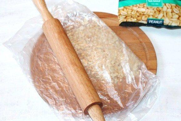 Кладем обжаренные орехи в пакет и измельчаем скалкой. Величина помола по вашему вкусу.