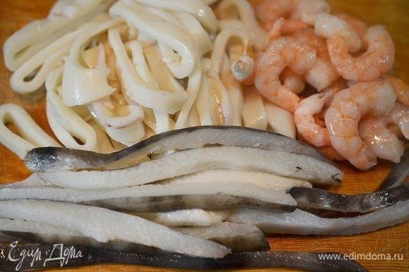 С рыбы срежьте филе и соедините с креветками и кальмарами.