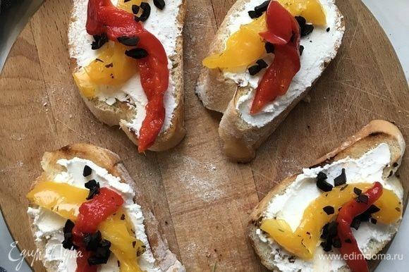 Выложите на хлеб творожный сыр, перец, маслины измельченные и украсьте зеленью.