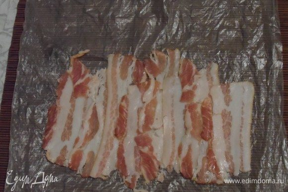 Выложить на циновку бекон по длинне ролла с сыром.
