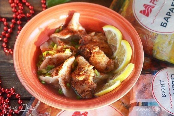 В тарелку выложите немного пельменей, сверху положите кусочек жареного рыбного филе. Подайте с ломтиками лимона и посыпьте молотым чили и зеленым луком.