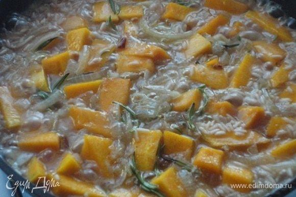 Лук мелко нарубить и обжарить в растительном масле до золотистого цвета. Добавить рис и позволить ему в течение 3 минут пропитаться маслом. Теперь можно выкладывать тыкву. Влить вино и дать ему покипеть пару минут. Затем добавить листочки розмарина и влить горячую воду. Посолить и оставить готовиться при медленном кипении.
