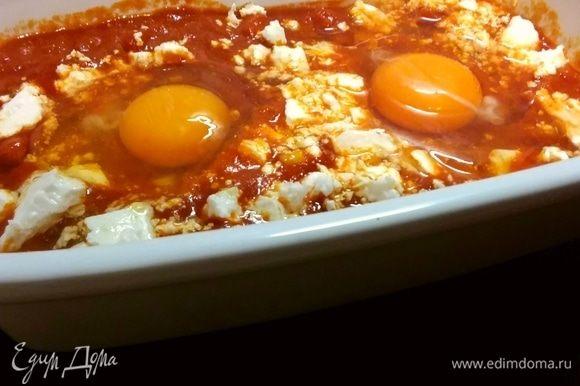 Чтобы закончить шакшуку индивидуально, предварительно разогрейте духовку до 180ºС. Разделите соус по формам для выпечки и распределите кубики феты в соусе. Сделайте углубления (по 2 на порцию) и выложите яйца в лунки. Выпекайте до тех пор, пока яйца не будут приготовлены по вашему вкусу. Это займет от 10 до 15 минут, но начните проверять их раньше, чтобы получить их в самый раз. Если желтки начнут немного укрепляться сверху, накройте форму листом фольги, но не прикасайтесь к желткам.