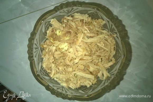 Затем отделяем сваренное куриное мясо от костей, нарезаем его тонкой соломкой и выкладываем в вазу для салата.