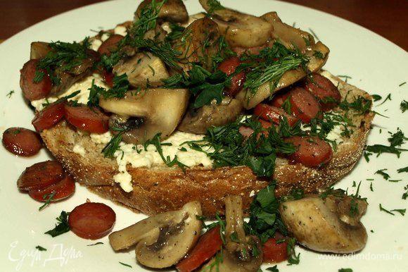 На хлеб выкладываем омлет, сверху грибы с охотничьими колбасками, посыпаем рубленой зеленью.