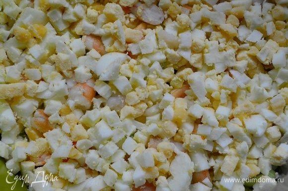 На креветки укладываем яйца, порезанные кубиками. Смазать соусом.