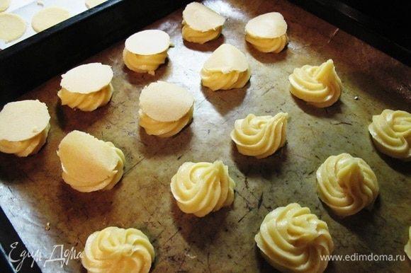 Готовое тесто отсадить на противень, на бумагу для выпечки, кружками диаметром около 5 см на расстоянии друг от друга, так как булочки будут сильно увеличиваться при выпечке. Достать из морозилки кружки первого теста и положить сверху на каждую булочку.