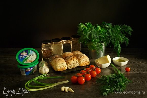 Подготовим необходимые ингредиенты. Нам нужны булочки, посыпанные маком, кунжутом, семенами льна и семенами подсолнечника или другие красивые зерновые булочки. Для фарширования 12 булочек небольшого размера нам потребуется 2 ванночки творожного сыра Hochland с зеленью. Также нам необходимы помидоры черри, чеснок, сливочное масло, оливковое масло, укроп или любая зелень, которая вам нравится. Ну, а если у вас на обед будет борщ, тем, кто окажется рядом с вами, просто повезло!