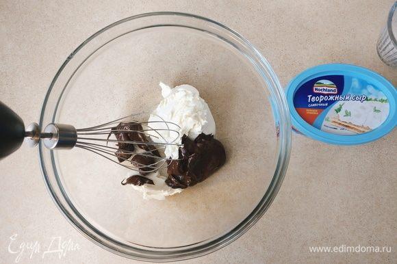 На минимальной скорости начать взбивать творожный сыр Hochland с растопленным шоколадом.