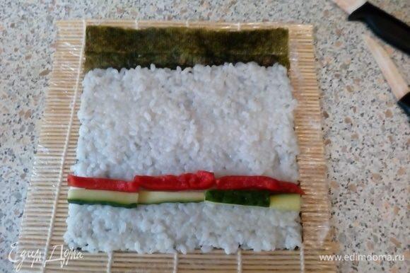 На шершавую поверхность нори выложить рис, оставив ~1–2 см листа не покрытым. Выложить бруски перца и огурца.