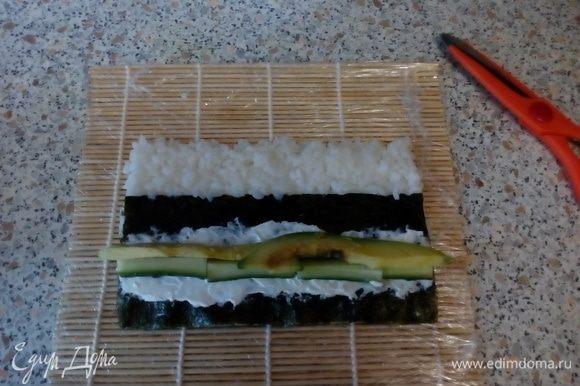 Смазать нори творожным сыром, выложить бруски авокадо и огурца.