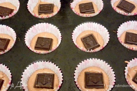 В бумажные формы для кексов положить часть теста. На нее положить кусочек шоколада.
