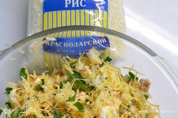 В миску выложить рис, курицу кубиками, сыр твердый и фету, зелень, соль и паприку. Все тщательно перемешать.
