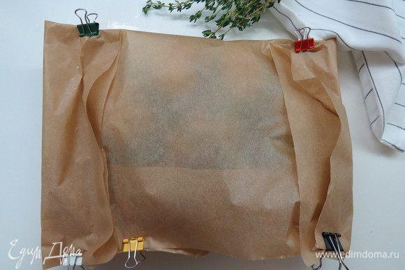 Накрыть картофель сверху свободной половиной пергамента, затем загнуть швы по бокам. Я для удобства использую канцелярские зажимы, но можно и просто сложить. Если конверт сложен не совсем герметично, это не страшно.