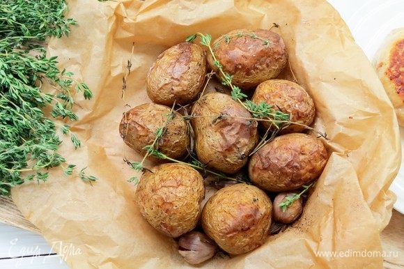Запекать картофель при температуре 200°С около 45 минут. Затем разорвать пергамент и подержать картофель еще 5-10 минут в духовке.