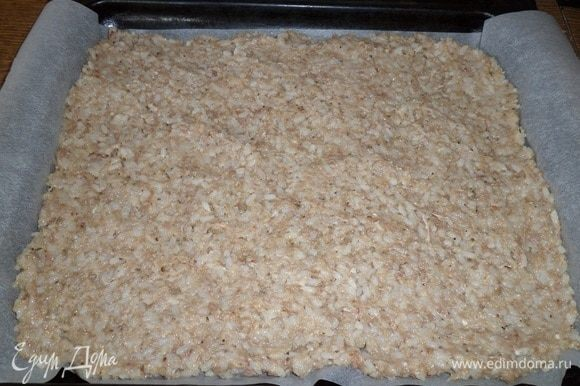 Противень застилаем пергаментом. На пергамент выкладываем рисово-мясную массу. Разравниваем.