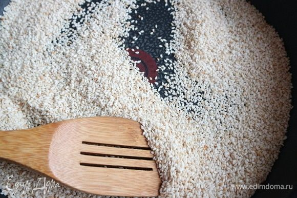 Обжарить семена кунжута на сухой сковороде до слегка золотистого цвета. Важно: не пережарить, потому помешивайте лопаточкой и следите за процессом.