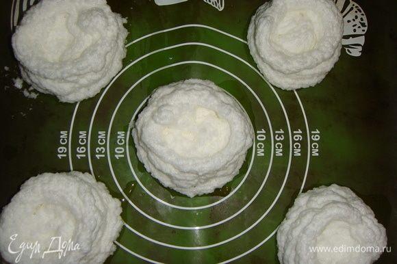 Противень застелить силиконовым ковриком или пергаментом. Белки выложить в кондитерский мешок и отсадить 5 «гнезд» на противень, делая повыше бортики.