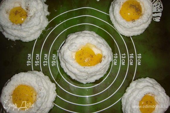 Аккуратно выложить желтки в середину каждого гнезда, посолить и поперчить по вкусу.