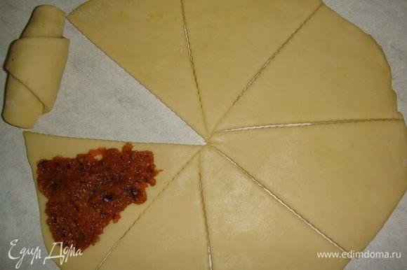 Стол слегка посыпать мукой. Раскатать одну часть теста в круг диаметром 25 см. Разрезать круг на 8 частей. На каждый треугольник выложить по одной чайной ложке начинки и распределить ее. Свернуть рогалики, начиная с широкого края.