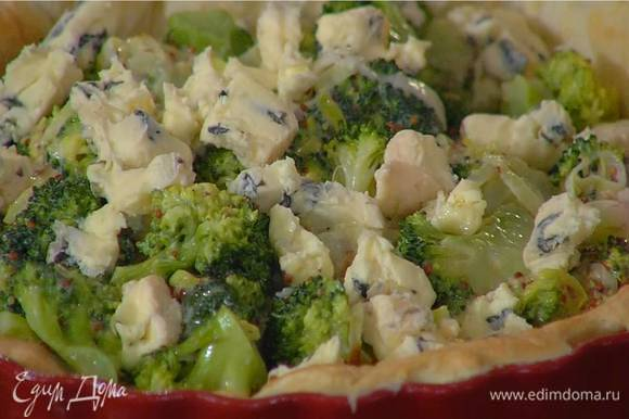 На подпеченный корж выложить овощную начинку, сверху разложить сыр.