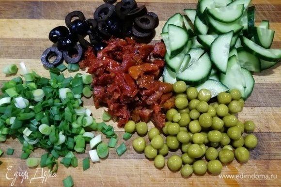 Подготовьте горошек, огурец, лук, вяленные томаты, маслины нарежьте. Перепелиные яйца отварите.