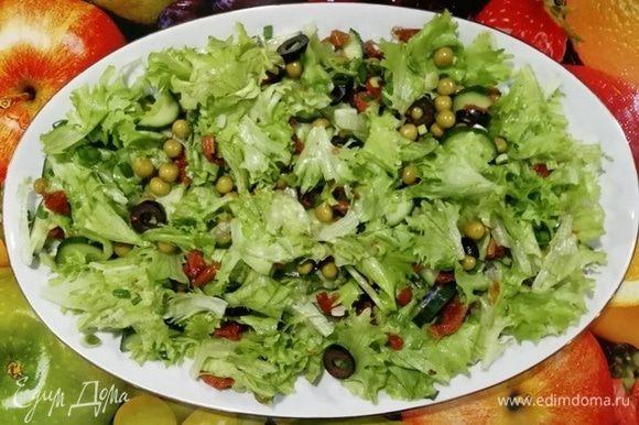 Смешать салат, горошек, огурец, маслины, лук и вяленные томаты. Выложить на блюдо.