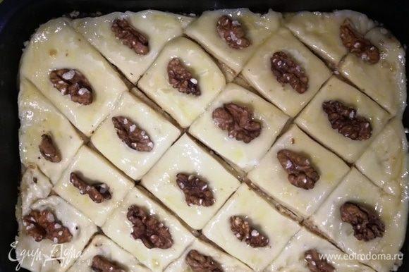 Смажьте тесто яйцом, выложите грецкие орехи и отправьте тесто в разогретую до 200°С духовку на 15 минут.