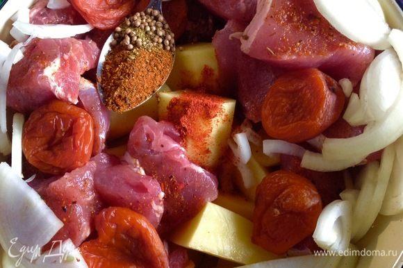 Включаем духовку на 200°С, пусть она греется, а мы начинаем свои приготовления. Картофель помыть, почистить, нарезать на 4 части, крупно. Мясо нарезать на куски, приближенные к размеру нарезанного картофеля. Луковицу нарезать пополам и потом слайсами. Все сложить в миску, посыпать специями для шашлыка, сухим чили, зернами кориандра, морской солью по вкусу, добавить мытую курагу в целом виде и чеснок тоже целыми зубчиками.