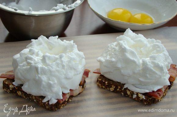 Сверху на бекон выложить взбитые белки в виде «шапочки», не забыв сделать в центре ямочку для желтков. Поставить бутерброды в разогретую до 180°С духовку минут на 10.