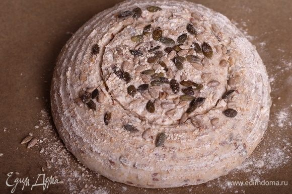 Примерно за 1,5 часа до выпечки хлеба начать разогревать духовку вместе с колпаком для выпечки или противнем (см. ниже п. 18 — как организовывать пар в духовке) до максимальной температуры. Запомните, что главное в выпечке хлеба — это жар и пар. Выжмите из своей духовки максимум. Моя разогревается до 250°С. Минимум для выпечки хлеба — 230°С. Если ниже — красивый хлеб может не получиться, надрезы не раскроются, корка будет бледной и «вялой». Как организовать пар? Можно использовать колпак для выпечки — это либо специальный набор (например, от Emile Henry), либо утятница с плоской крышкой, либо толстостенная металлическая кастрюля и камень для выпечки. Вообще, без камня для выпечки сложно получить ровный, хорошо пропеченный хлеб с красивой корочкой. Если не можете приобрести колпак, то камнем все же рекомендую обзавестись. Также пар можно сделать другим способом — начать разогревать духовку вместе с противнем (либо небольшой сковородкой, установленной на самое дно духовки). После того, как хлеб скидывается в духовку на камень, без промедления сразу же на раскаленный противень или сковородку выливается 1 стакан кипятка. Начнется активное испарение воды. Не обожгитесь только, будьте осторожны! Итак, перенести расстоенную заготовку на бумагу для выпечки, сделать надрез или надрезы. Я сделала для круглого хлеба 1 надрез лезвием по кругу.