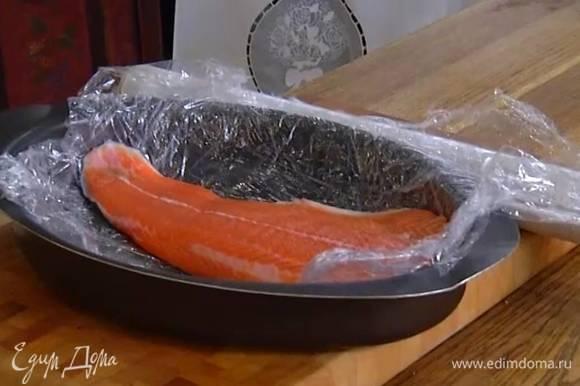 Форму выстелить пищевой пленкой и выложить рыбу.