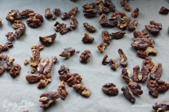 Грецкие орешки выложите на противень на бумагу для выпечки, запеките в духовке около 10–15 минут при 200°С до появления аромата и легкого потемнения орешков.