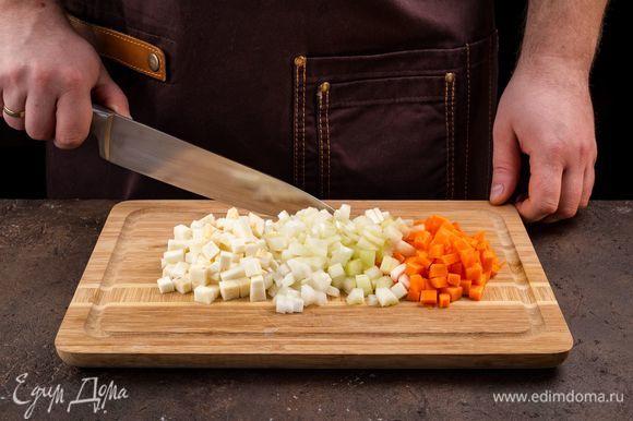 Очистите репчатый лук, сельдерей, корень сельдерея, морковь и нарежьте кубиками. В сотейнике с толстым дном разогрейте 4 ст. л. оливкового масла и обжарьте лук до прозрачности. Морковь и корень сельдерея добавьте в сотейник и томите все вместе 5 минут.