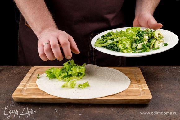 Приступаем к сборке кесадильи. Тортилью предварительно подогрейте на сковороде или в микроволновке. Положите тортилью на доску. На лепешку выложите зелень.