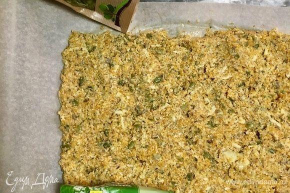 Духовку разогреть до 180°С. Противень выстелить бумагой для выпечки. На него в форме прямоугольника выложить тесто.