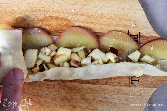Делаем розы. Полоску тесто смазываем маслом, посыпаем тонким слоем орехов и яблок. Полукольца яблок в ряд кладем по верхнему краю в длину, чтобы 0,5 см яблока с кожицой выступала над тестом. Сворачиваем штрудель трубочкой, предварительно 1 см нижнего края завернув. Вертикально ставим на лист с бумагой для запекания полукольцами яблок наверх.