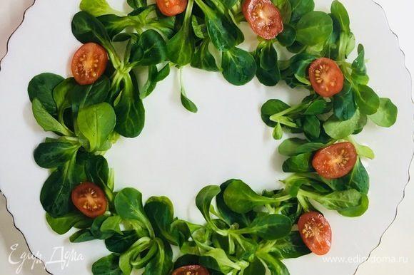 На салат выкладываем помидоры черри, предварительно разрезанные на две части.
