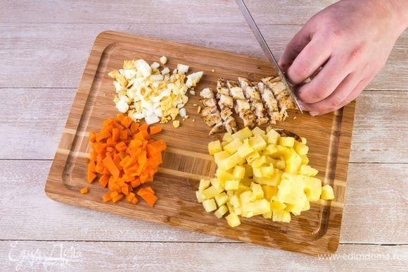 Нарежьте картофель, морковь, яйца и куриное филе одинаковыми кубиками.