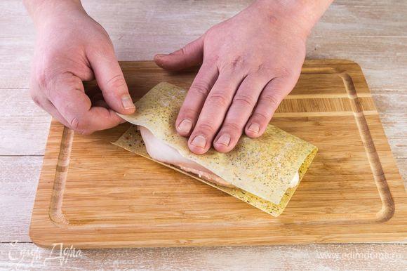 Положите филе на половину листа MAGGI®, закройте второй половиной и прижмите рукой.