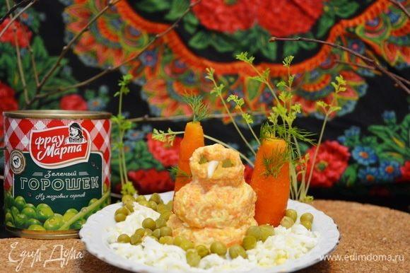 Формируем из массы плотные шарики, делаем весновика. Глаза делаем из зеленого горошка ТМ «Фрау Марта», нос из яичного белка. Вокруг нашего яркого героя выкладываем зеленый горошек, который символизирует первую весеннюю траву в проталинах снега. Оригинальная подача простой закуски по-весеннему. Приятного аппетита!