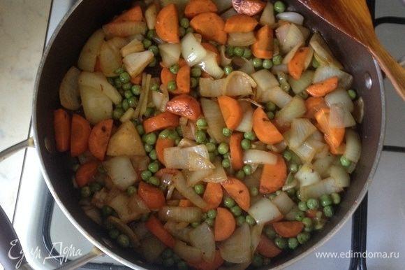 В сотейнике, где жарились ребра, добавить растительное масло и обжарить морковь, лук и зеленый горошек буквально пару минут до золотистости.