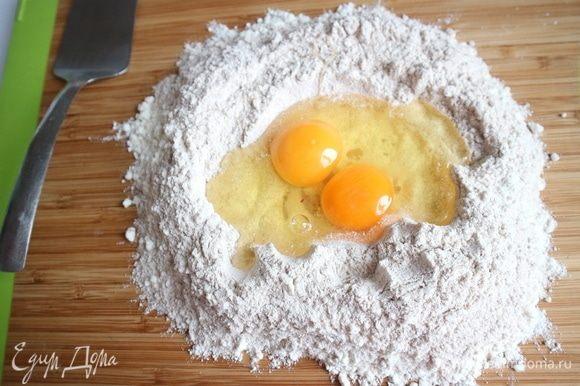 Смешать два вида муки, сделать «колодец» из муки на рабочей поверхности, разбить туда куриные яйца, сначала два яйца, здесь яйца среднего размера. Перемешать немного, можно с помощью вилки, я пользовалась металлической лопаткой.