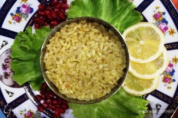 Готовим блюдо к подаче. На листы салата устанавливаем кулинарное кольцо, выкладываем рис. Украшаем дольками лимона и зернами граната (или на свое усмотрение).